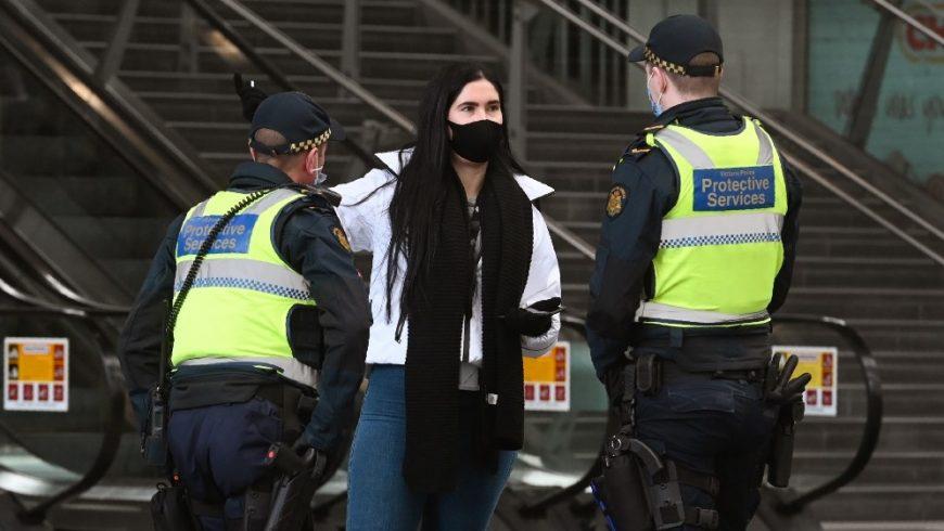 Petugas layanan perlindungan berbicara dengan seorang wanita di Stasiun Southern Cross, di Melbourne pada 7 Agustus 2020, saat kota tersebut dikunci secara ketat. (Foto AFP/ Al Jazeera)